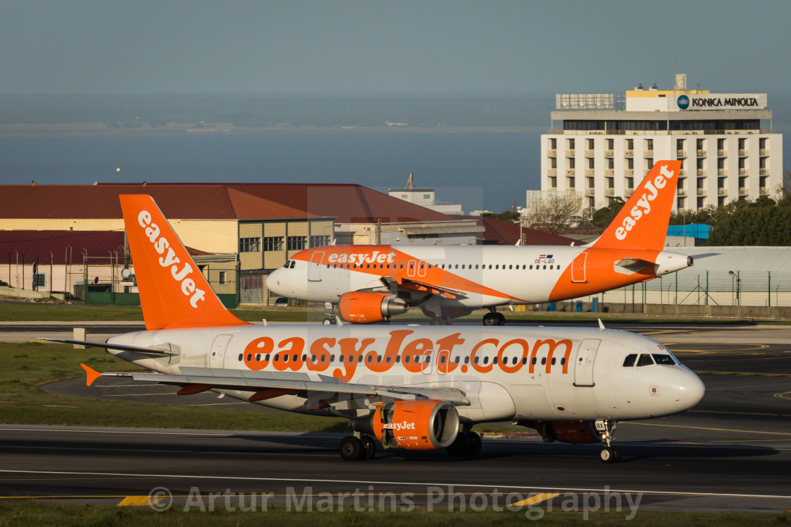 """easyJet airliners cross paths at Lisbon Airport"" stock image"