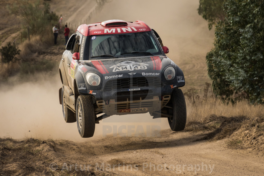 """A Mini All4Racing off-road race car makes a jump on a dirt road"" stock image"