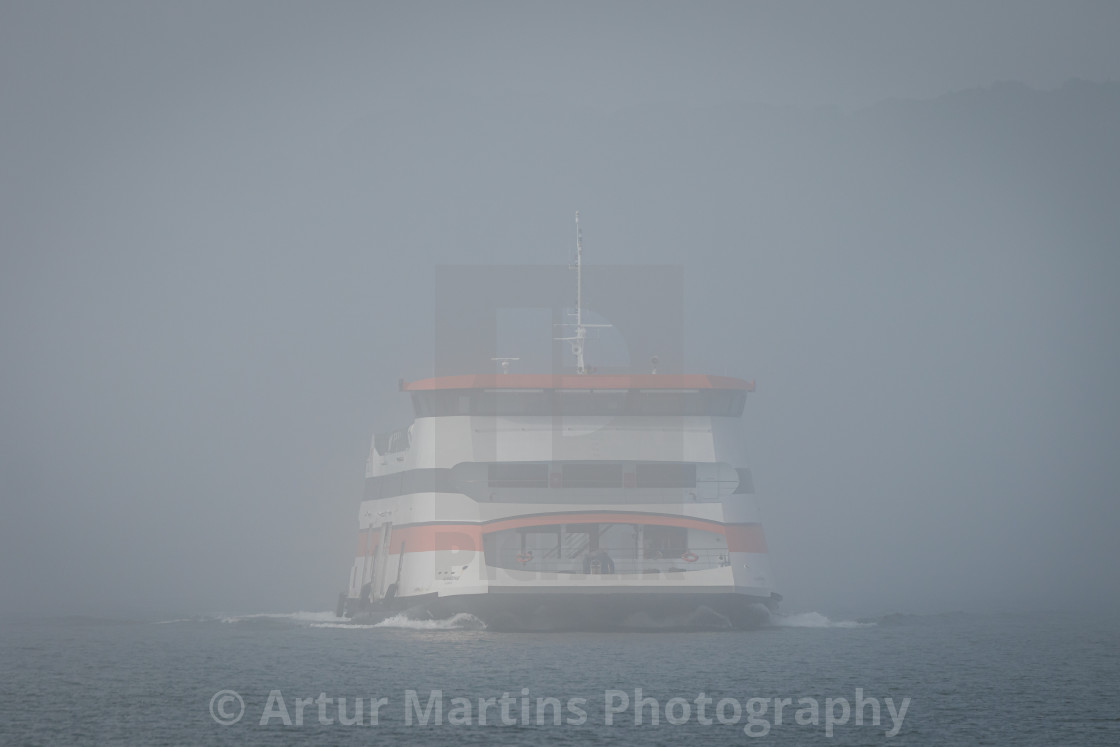 """Portuguese catamaran ferryboat Almadense crossing the river under fog"" stock image"