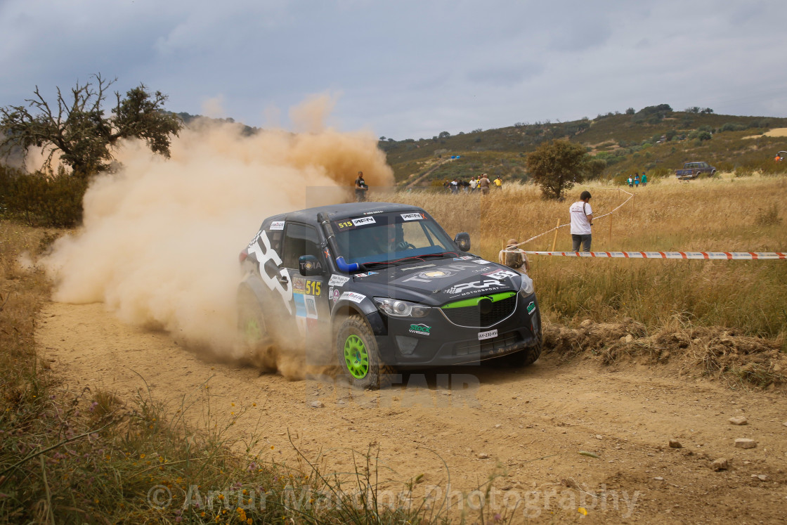 """A Mazda Proto off-road race car creating a cloud of dust"" stock image"
