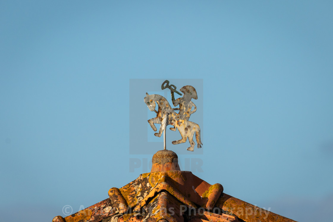 """Old brass weather vane on a rooftop"" stock image"
