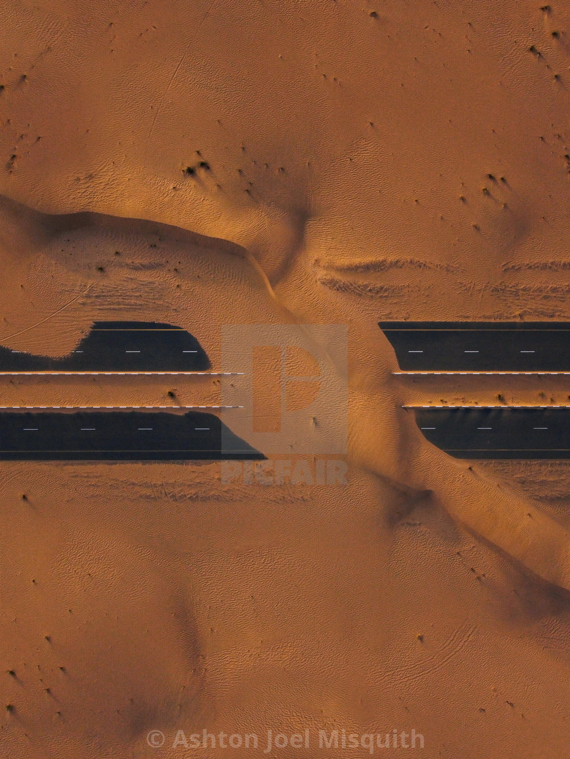 """Aerial shot of abandoned roads in Dubai covered in sand."" stock image"