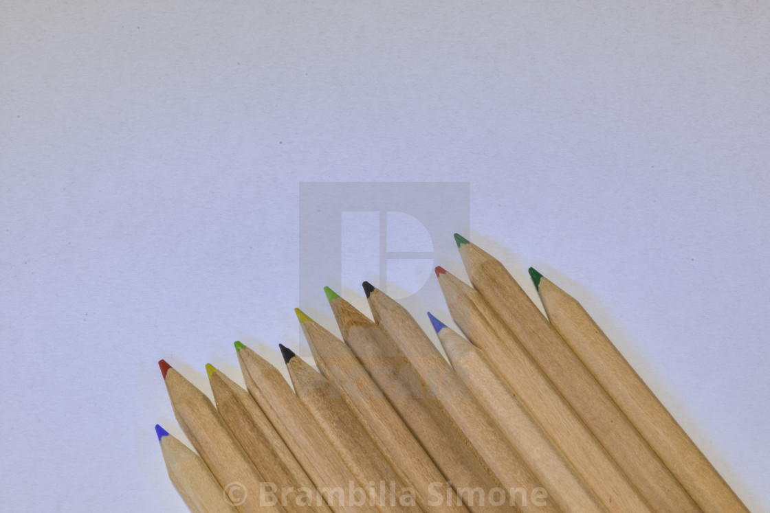 colored crayons lined up on a white pape , horizontal image