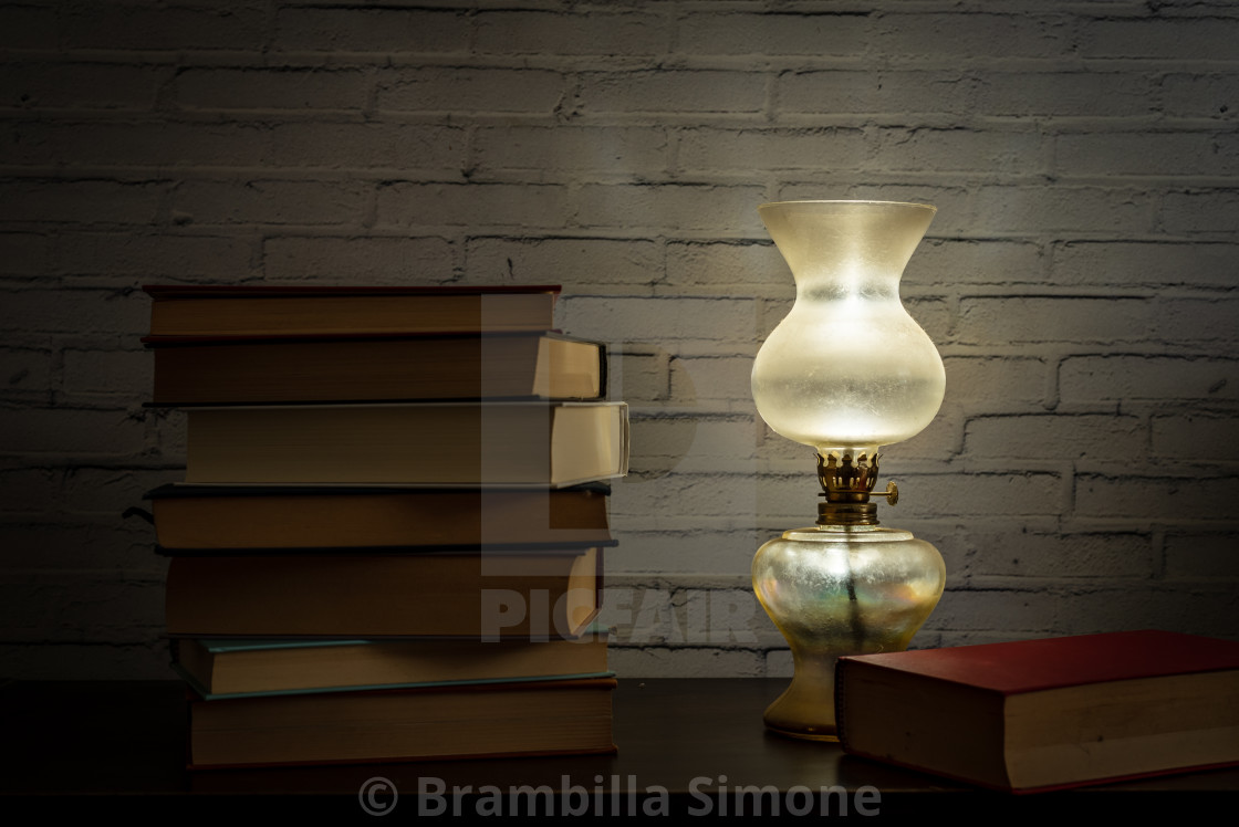 The light of an oil lamp illuminates books placed on a dark wood
