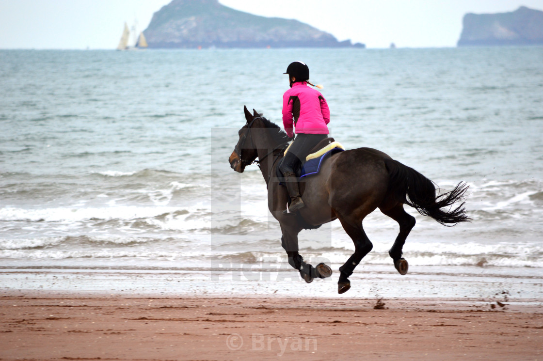 """""""Horse and Rider at the gallop on seaside beach"""" stock image"""