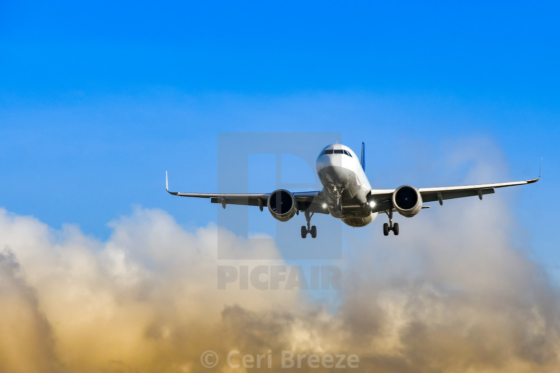 """Passenger jet coming into land at an airport against blue sky and colourful clouds"" stock image"