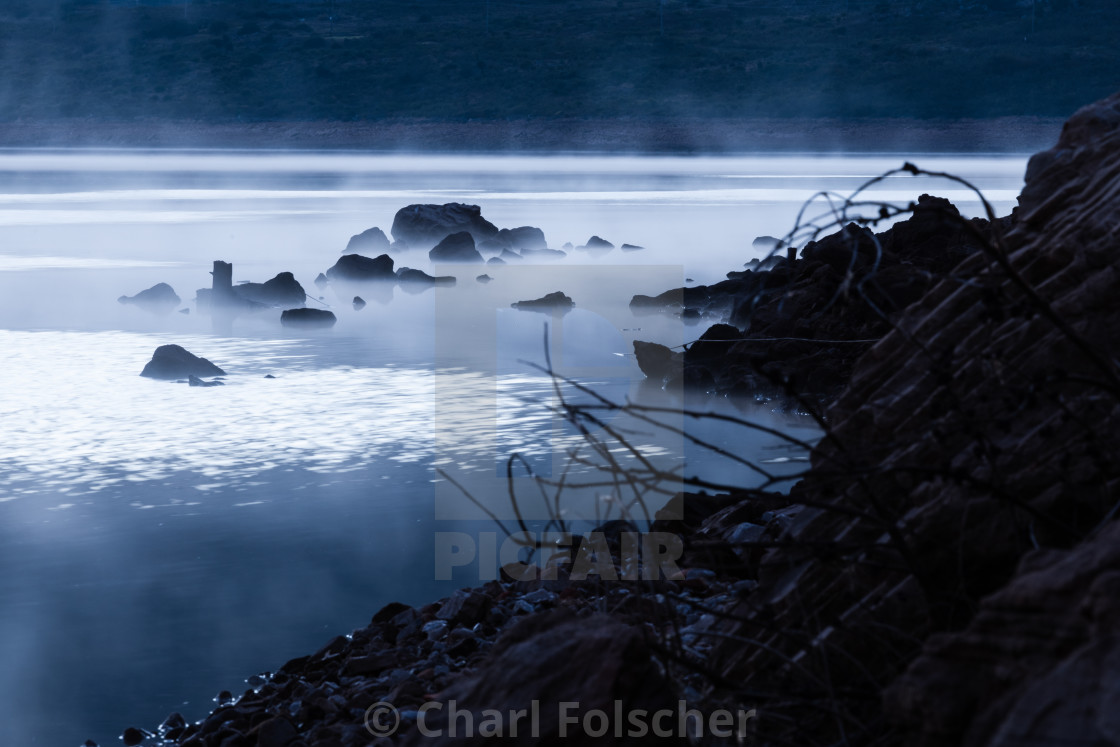 """""""Rocks in a lake or ocean scene sticking out above mist"""" stock image"""