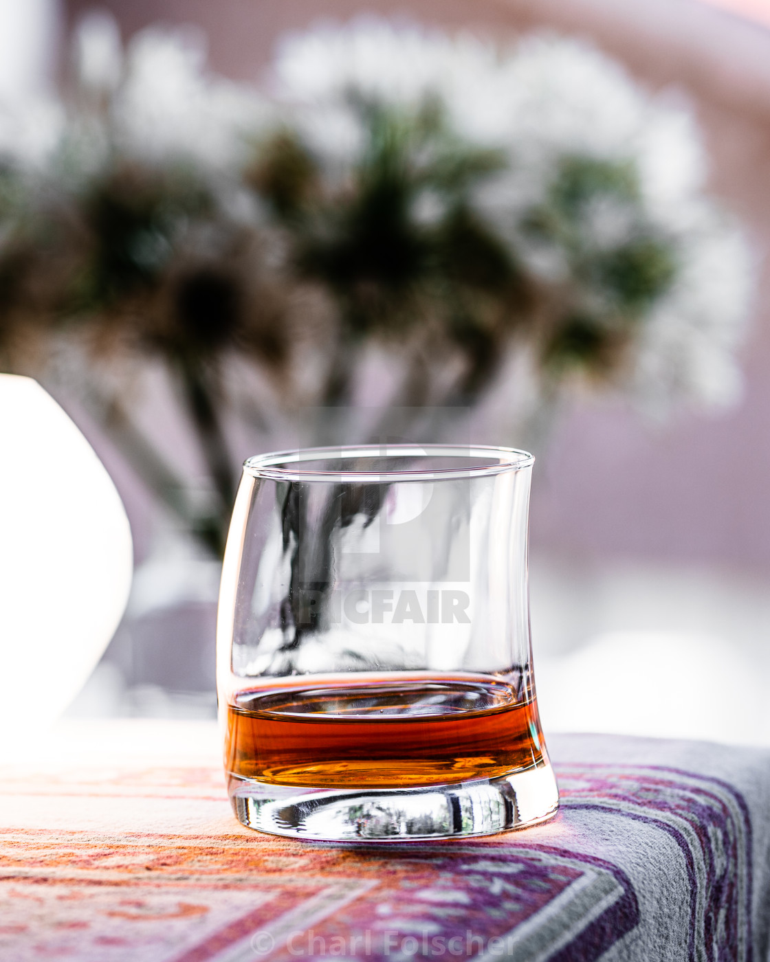 """""""A bokeh shot of glass of whiskey on a table"""" stock image"""
