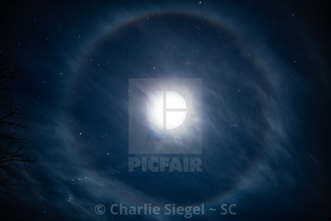 """Lunar Halo Surrounding the Moon in a Starry Sky"" stock image"
