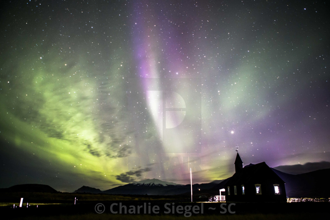 """Angelic Form in Purple and Green Aurora borealis over Budir Church Iceland"" stock image"