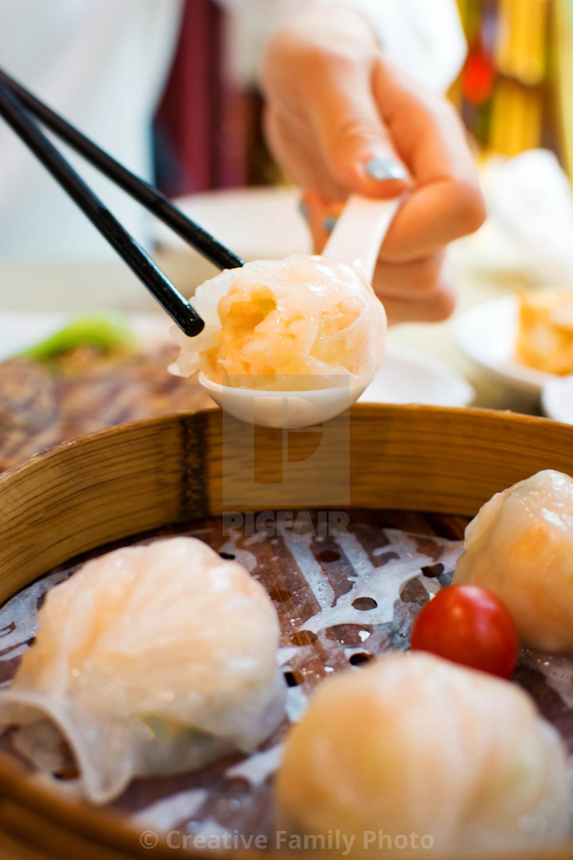 """Girl taking shrimp dumpling with chopsticks"" stock image"