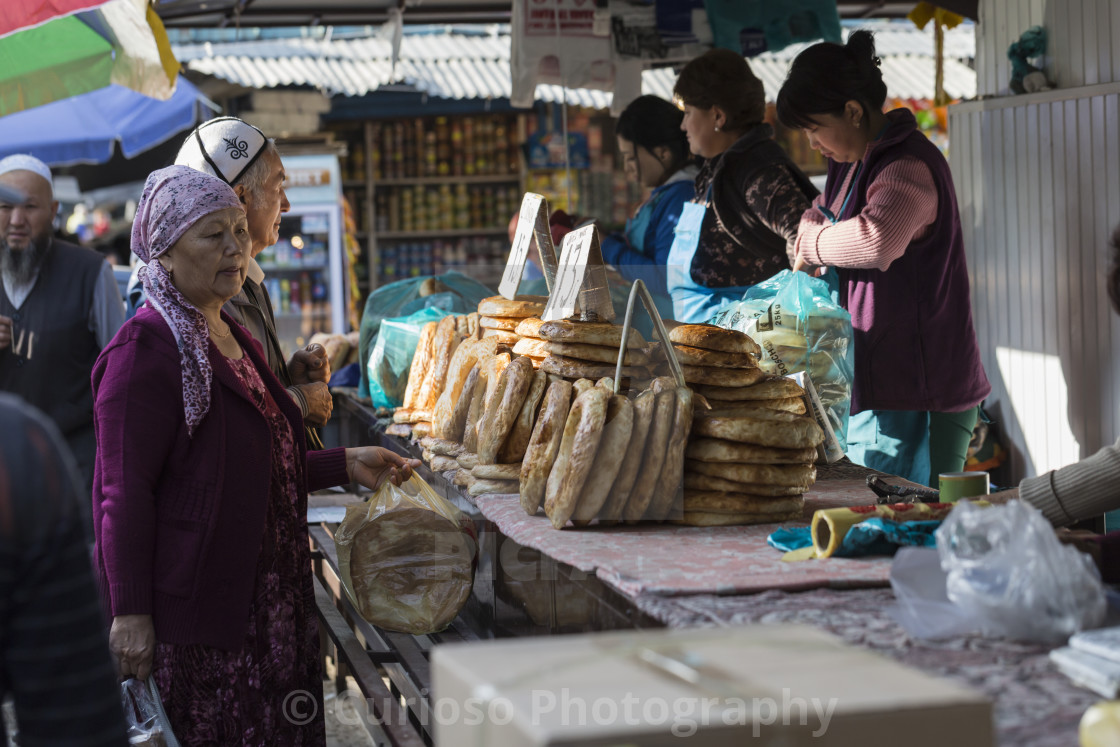 """BISHKEK, KYRGYZSTAN - SEPTEMBER 27, 2015 : Woman selling Asian style bread in..."" stock image"