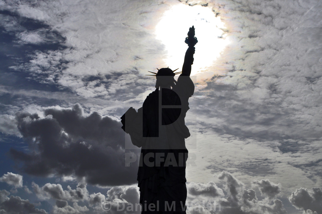 """Statue of Liberty in Paris France (Pont de Grenelle) silhouetted with sun shining through clouds."" stock image"