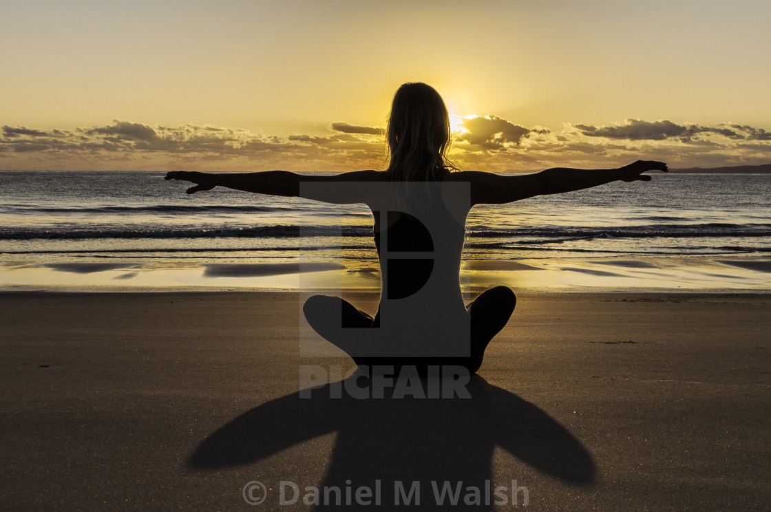 """Yoga and meditation on the beach at sunrise ."" stock image"
