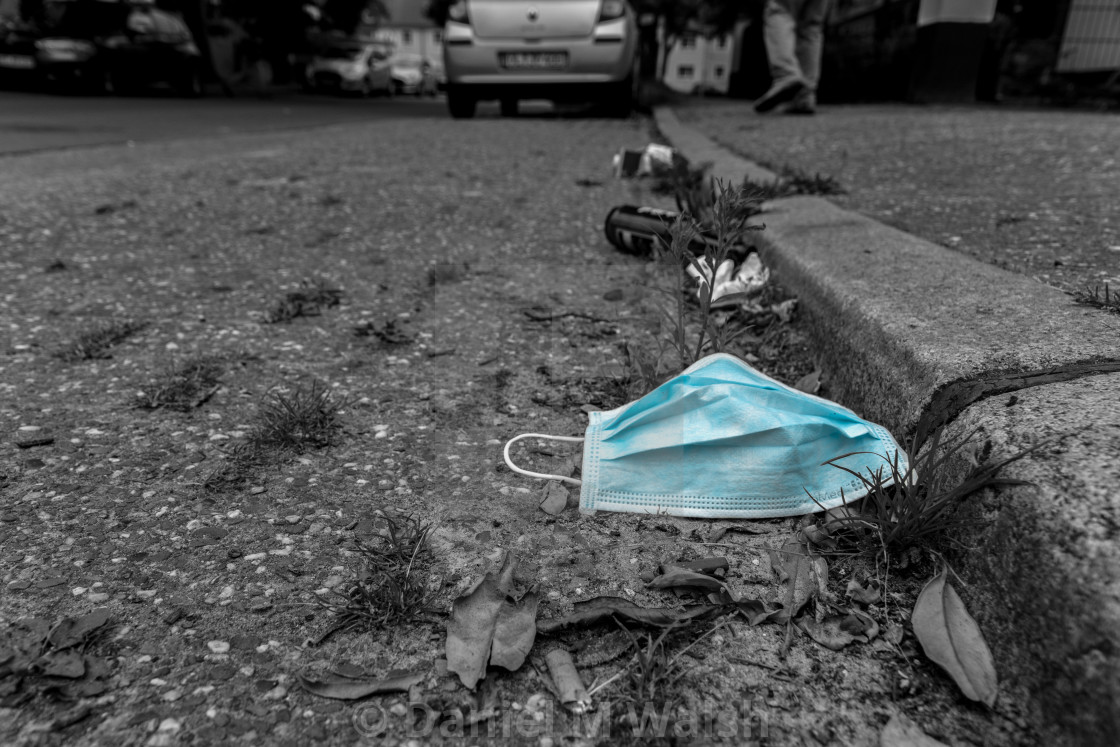 """Coronavirus face mask discarded and lying on the street in black and white with blue colored mask."" stock image"