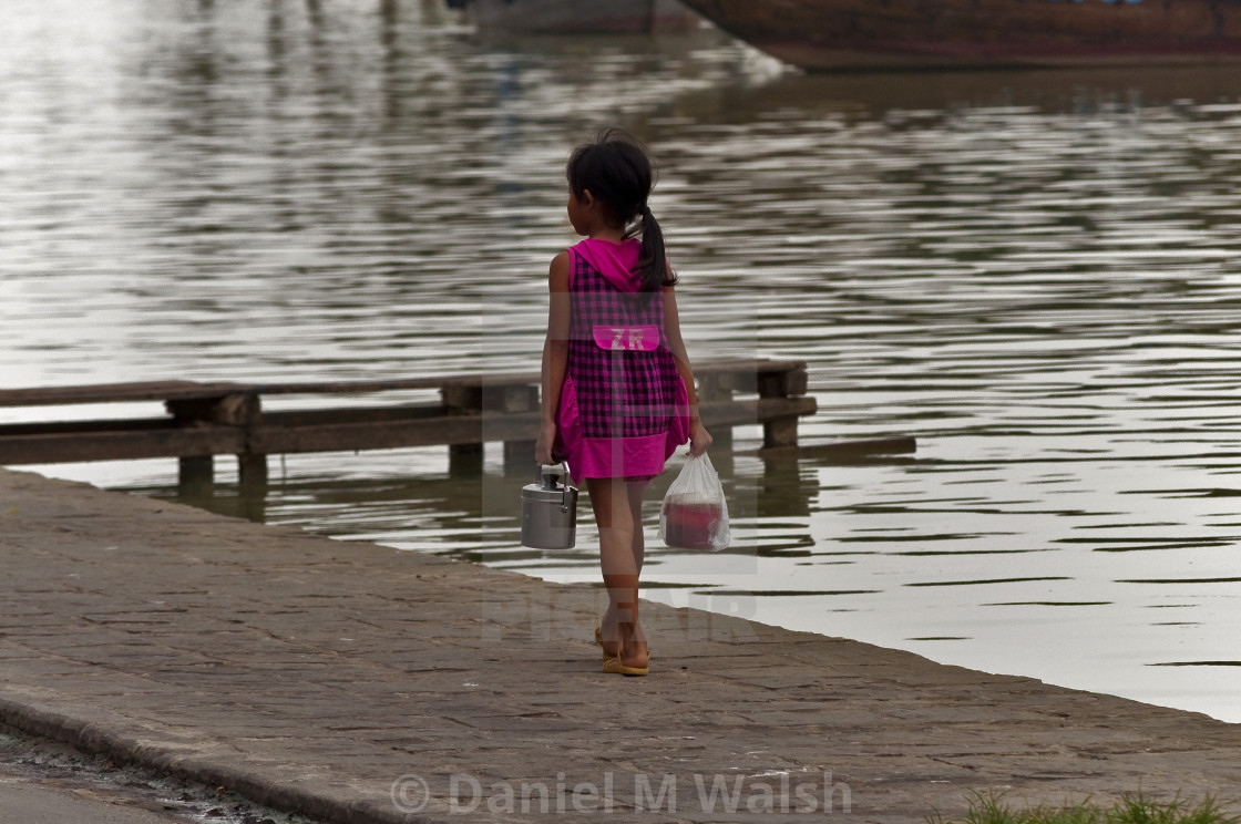 """""""A young Vietnamese girl walking home carrying food."""" stock image"""