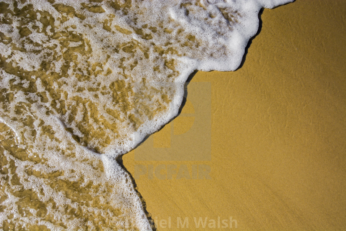 """Ocean water and foam washing up over golden sand"" stock image"