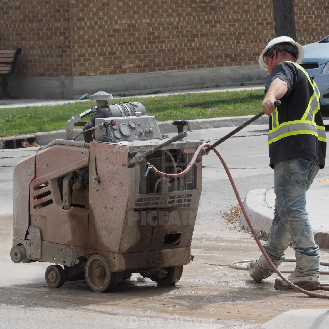 """Workman using a pavement saw"" stock image"