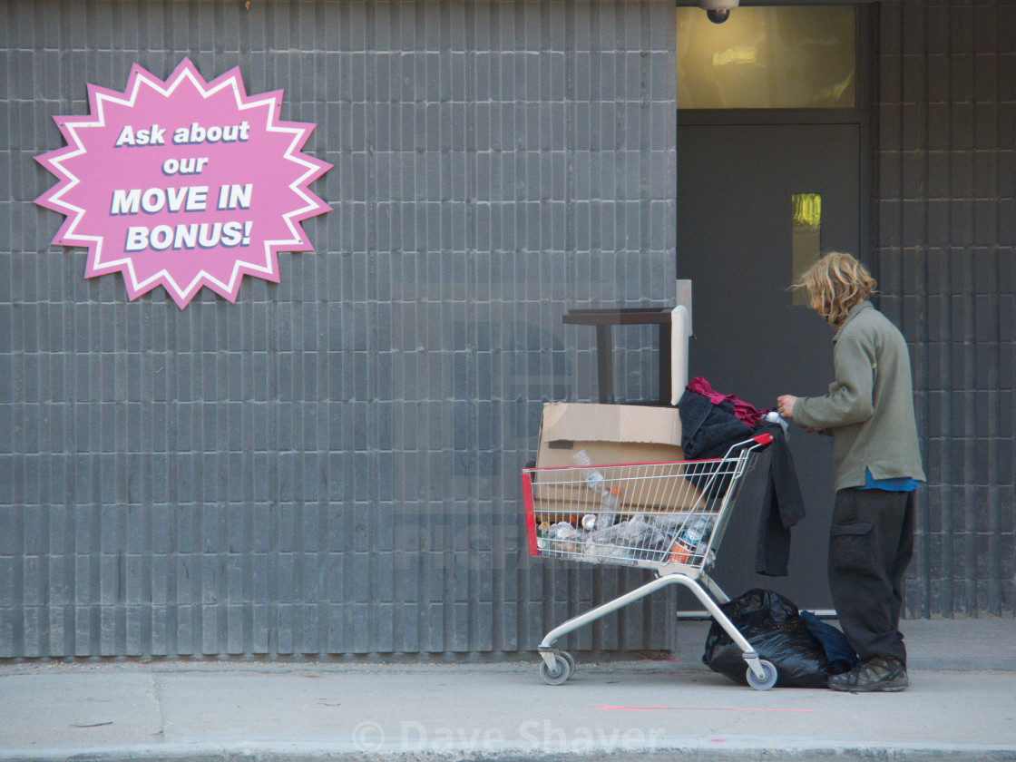 """""""Homeless man passing by apartment promotion sign"""" stock image"""