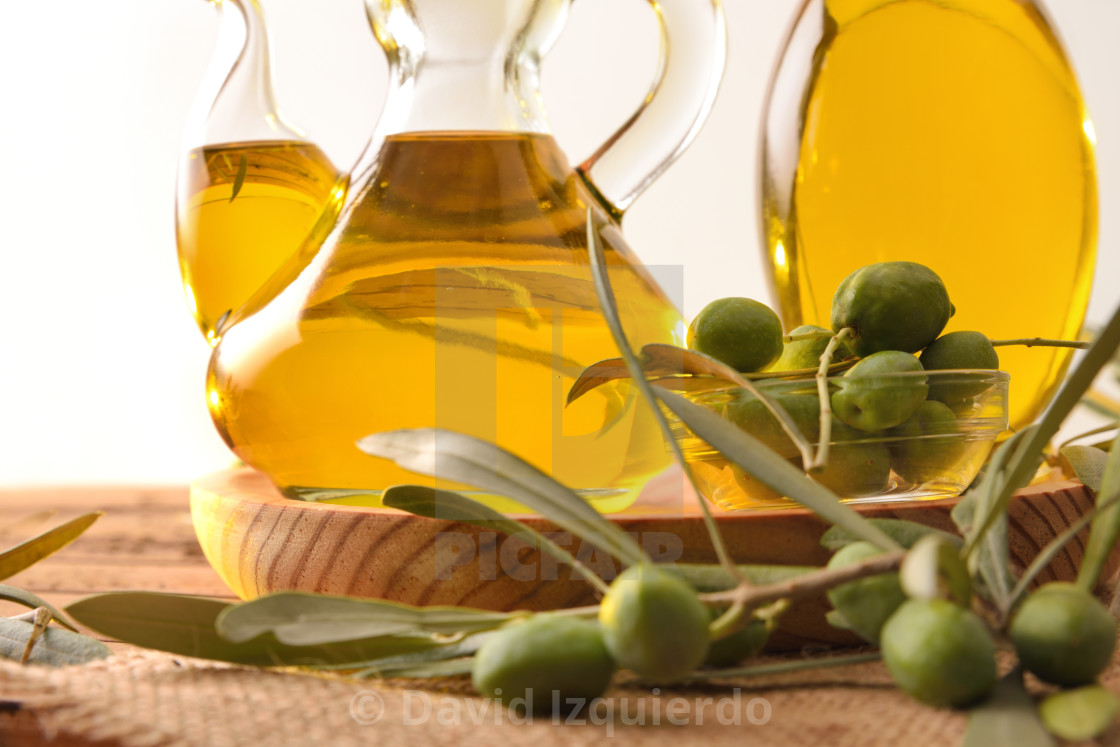 """""""Olive oil dispensers detail on wooden table with olives isolated"""" stock image"""