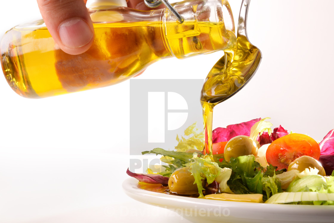 """Pouring olive oil from oil dispenser on salad close up"" stock image"