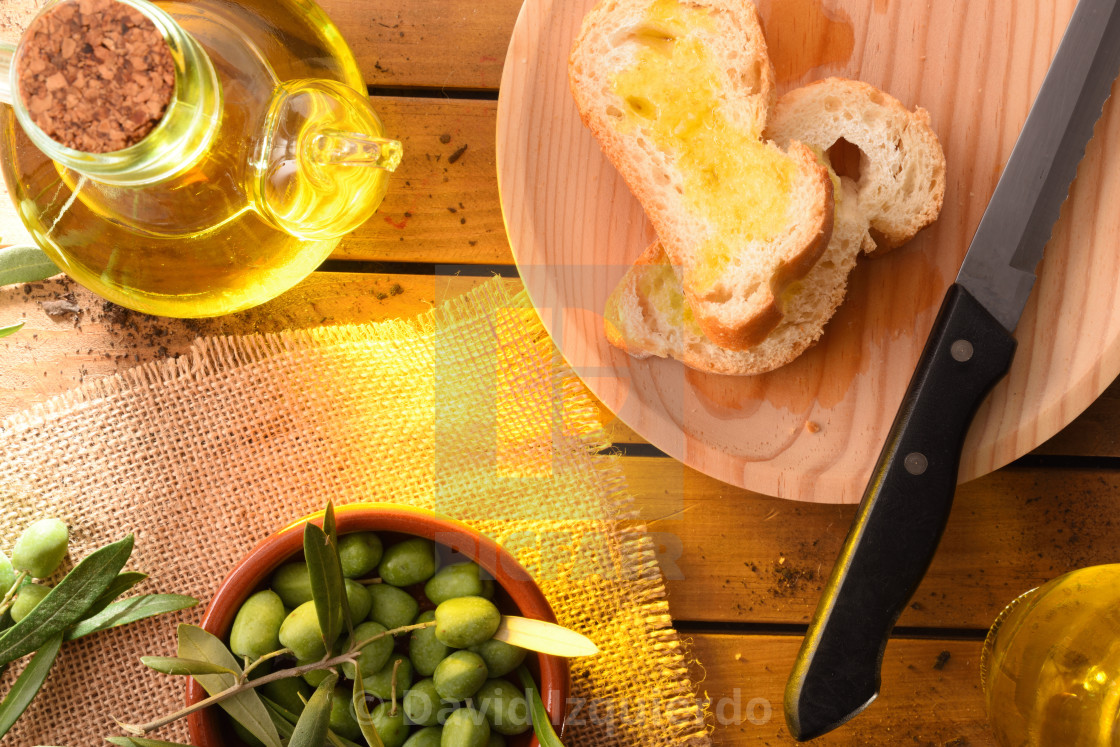 """""""Slices of bread with oil on wooden table countryside detail"""" stock image"""