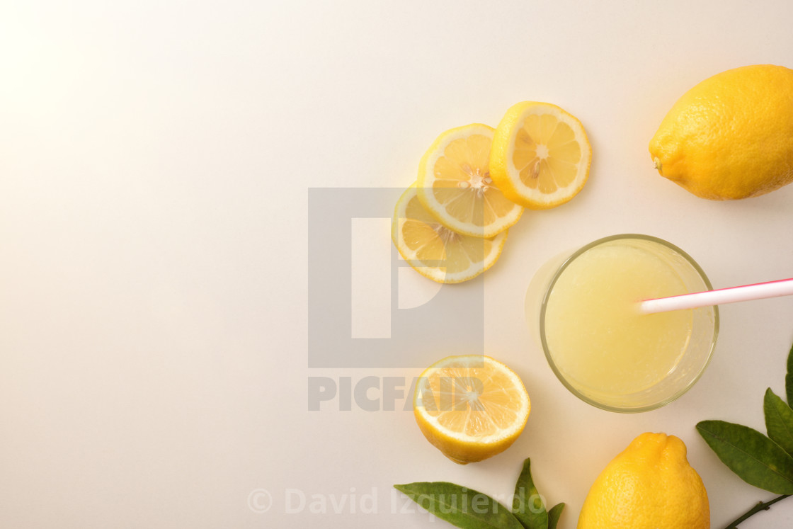 """""""Cut and sliced lemon and juice on white table top"""" stock image"""