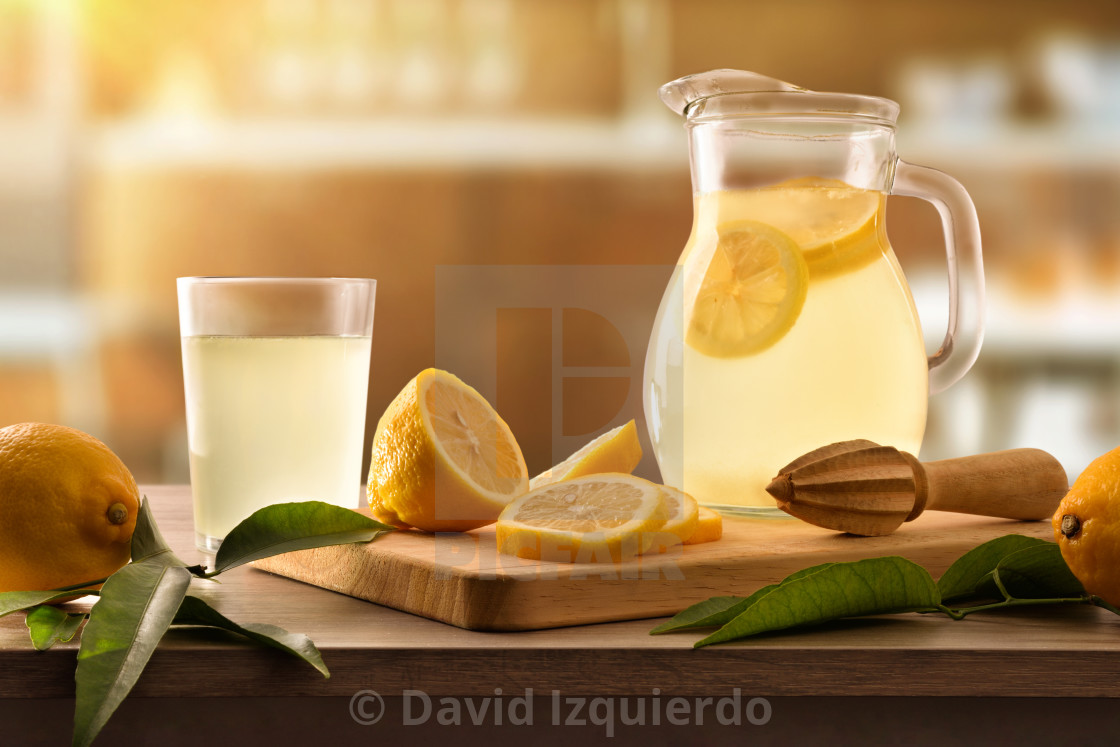 """Freshly lemon juice with utensils on wooden kitchen bench front"" stock image"