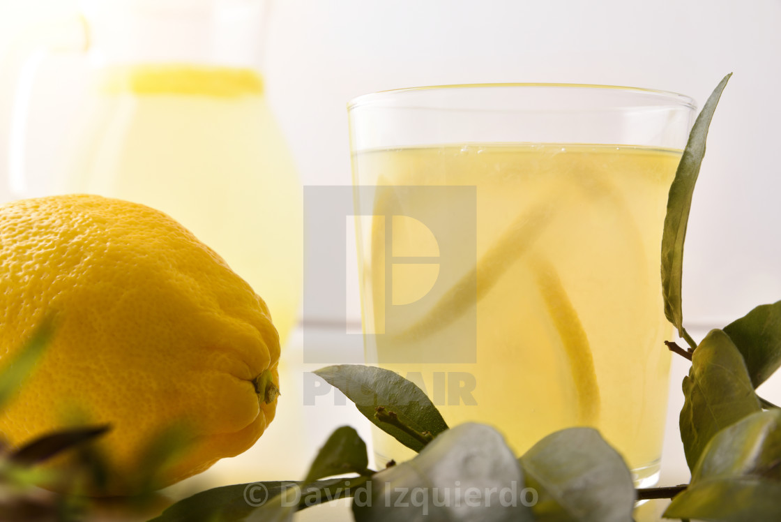 """Glass with freshly squeezed lemon juice detail isolated white"" stock image"