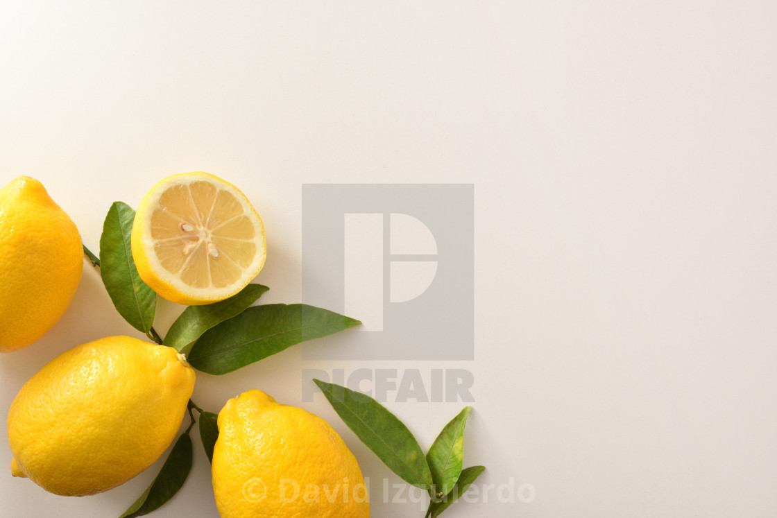 """""""Group of lemons with leaves and half lemon on table"""" stock image"""
