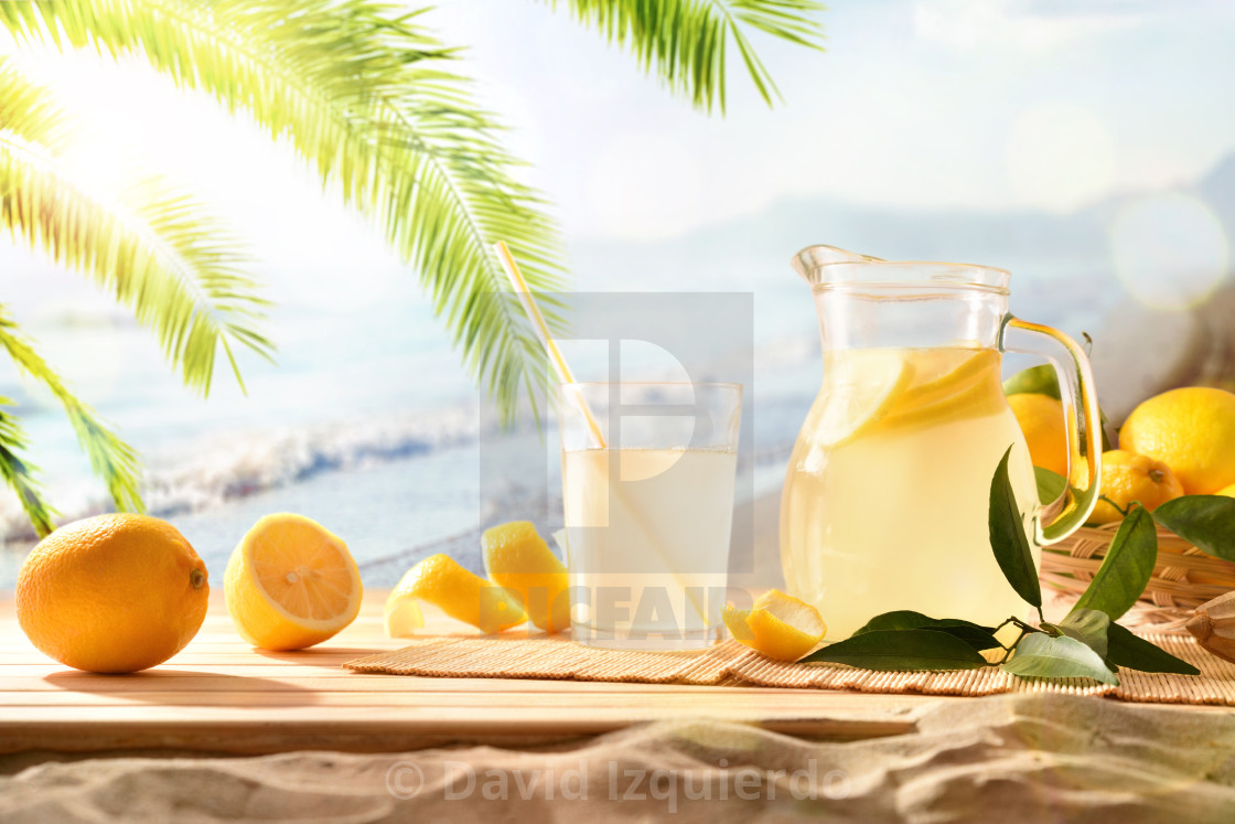 """""""Jug and glass with squeezed lemon juice on the beach"""" stock image"""