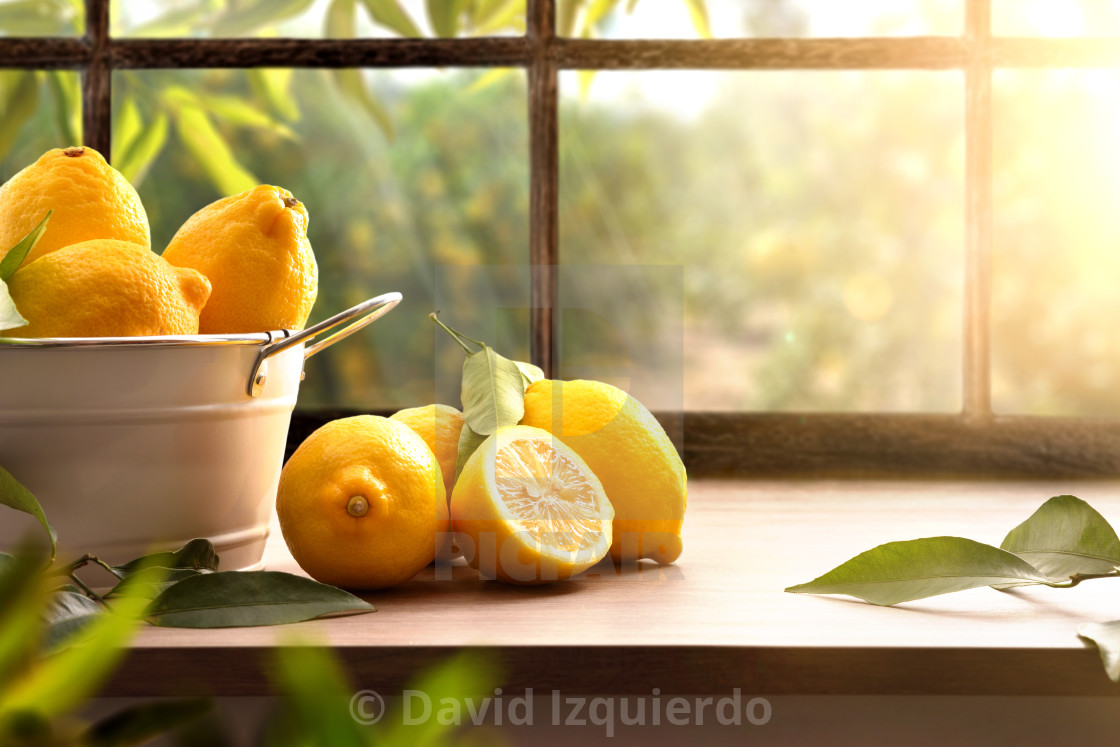 """""""Lemons basket on kitchen with window and orchard outside"""" stock image"""
