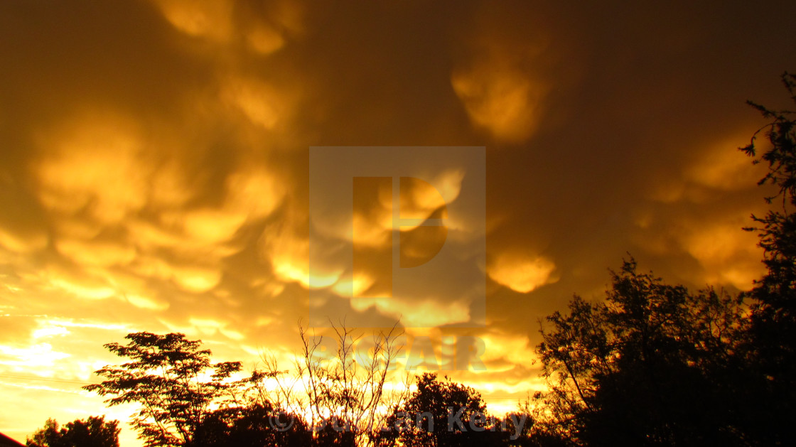 """""""Post thunderstorm cumulus clouds at sunset"""" stock image"""