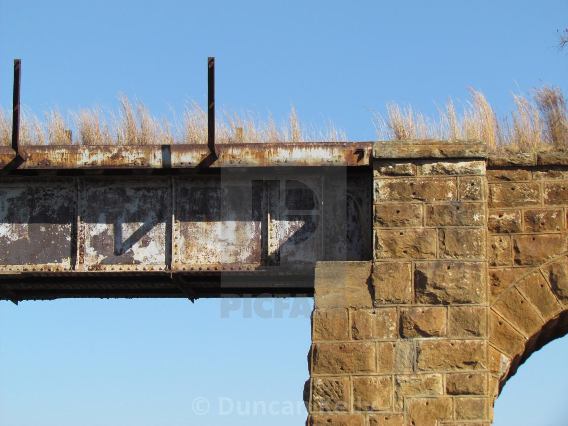 """Detail of an old sandstone and steel railway bridge"" stock image"