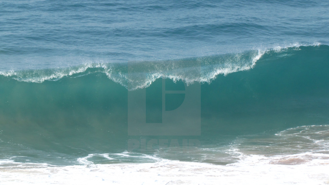 """""""A clear, breaking ocean wave on a sunny day."""" stock image"""