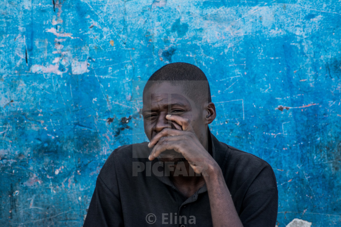 """Man by blue wall"" stock image"