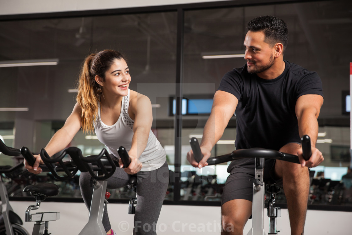 """Cute young couple flirting at a gym"" stock image"