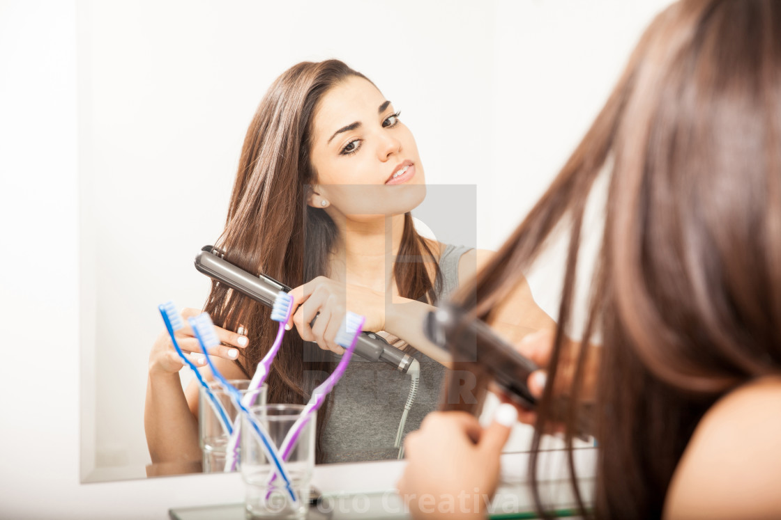 """Woman straightening her hair"" stock image"
