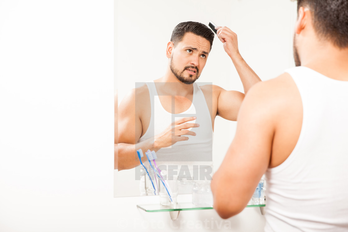 """Good looking guy combing his hair"" stock image"