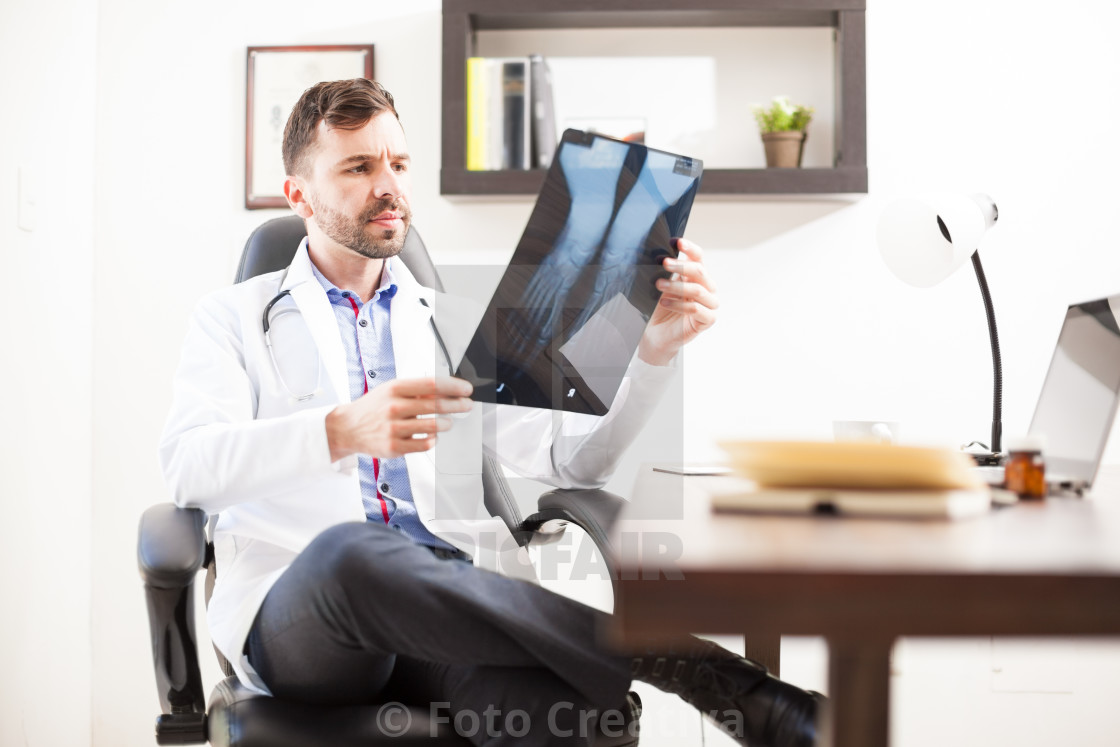"""Orthopedist looking at x-rays from a patient"" stock image"