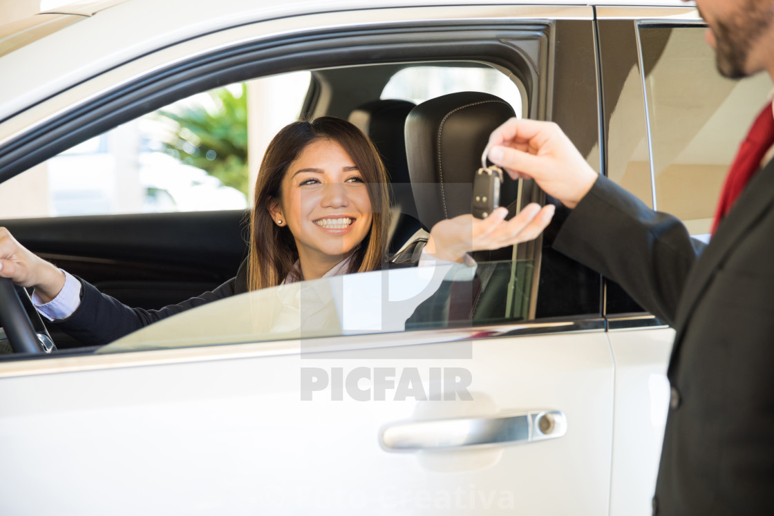 """Excited woman at a car dealership"" stock image"