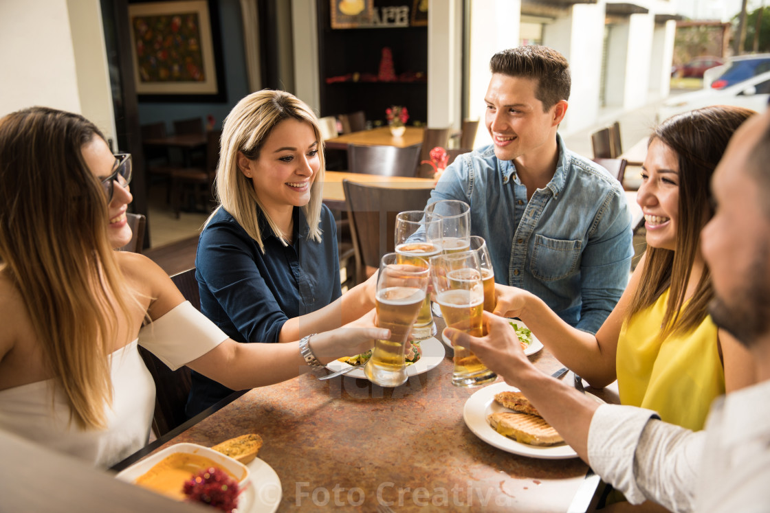 """Young adults making a toast with beer"" stock image"