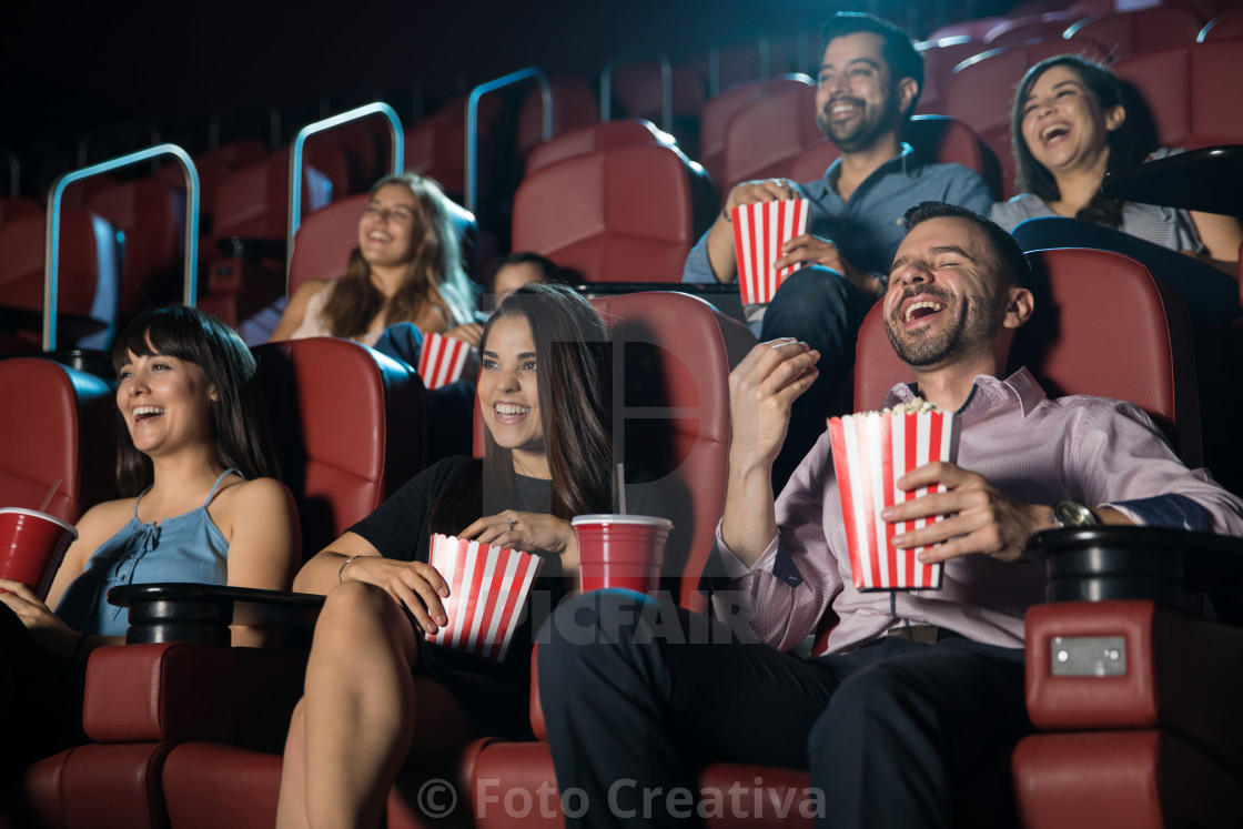 """Group of people laughing at the movie theater"" stock image"