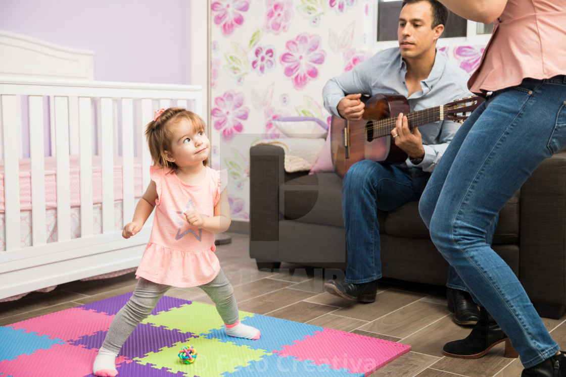 """Happy girl dancing to her mom and dad"" stock image"