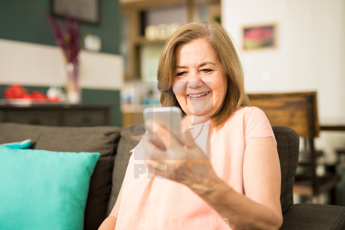 """Senior woman watching video on her phone"" stock image"