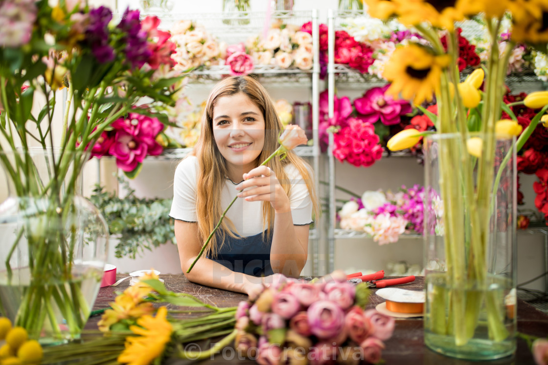"""Female florist holding a rose"" stock image"