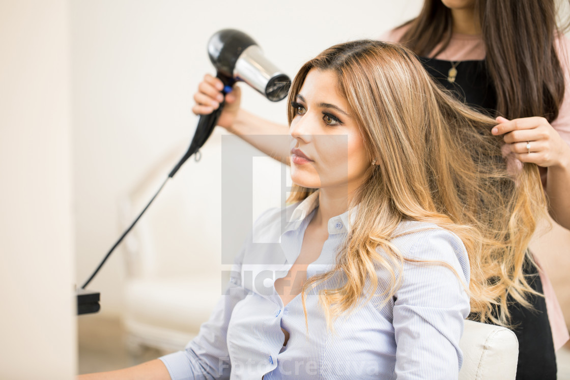 """Woman getting her hair dry in a salon"" stock image"