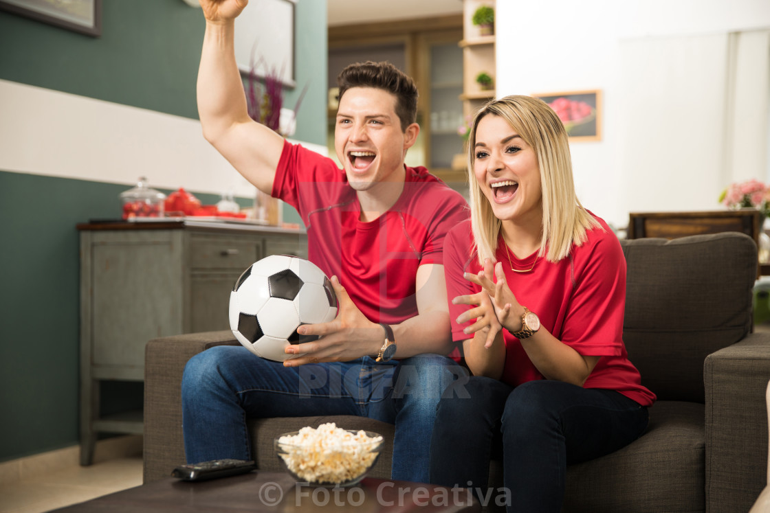"""Excited soccer fans watching game"" stock image"