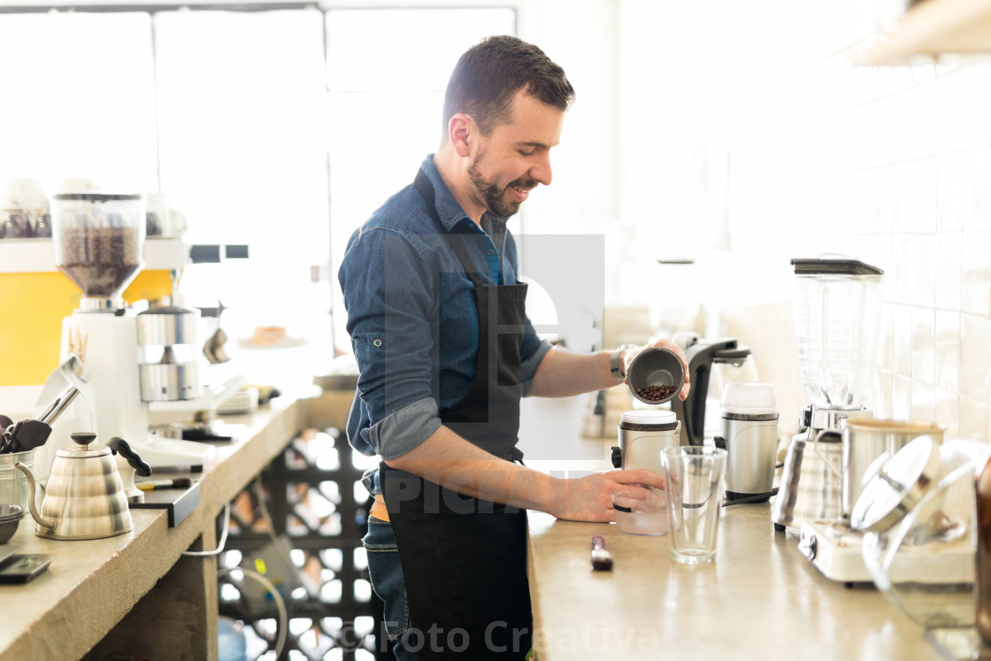 """Happy barista making a cup of coffee"" stock image"
