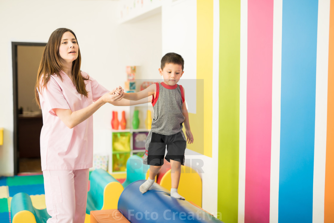"""Therapist helping a kid with balance"" stock image"